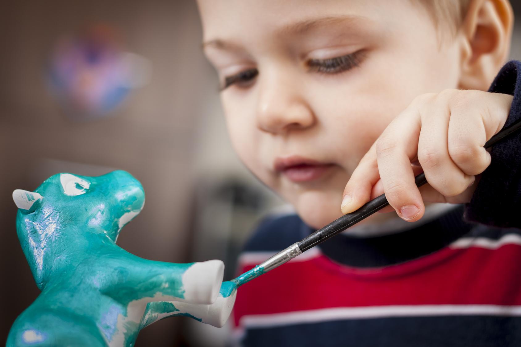 Detail of boy painting ceramic figure