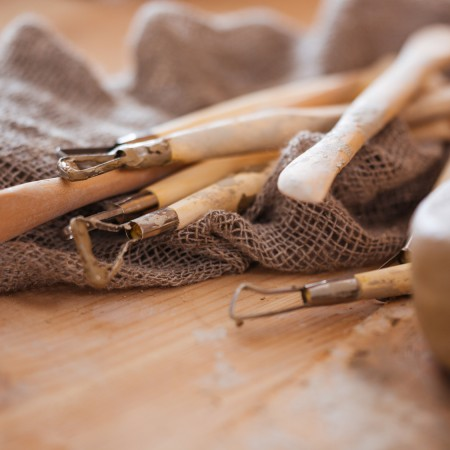 Set of dirty craft sculpting tools in pottery workshop
